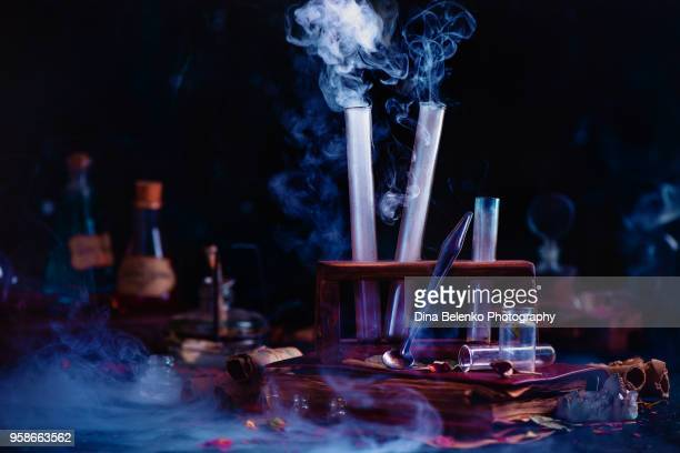laboratory scene with test tubes in a wooden stand with rising smoke, scrolls, potion bottles and notes. alchemy concept with copy space. - alchimie photos et images de collection