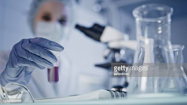 laboratory scientist working with biohazardous samples. focus on hand with test tube - world health organisation stock pictures, royalty-free photos & images