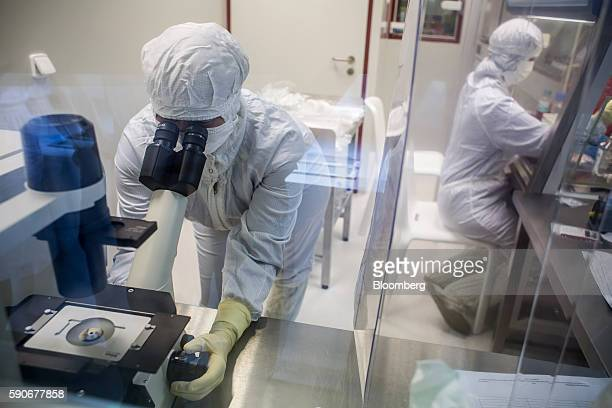 A laboratory specialist uses a microscope to check cells during the last phase of vaccine manufacture inside a clean laboratory at the Sotio AS...