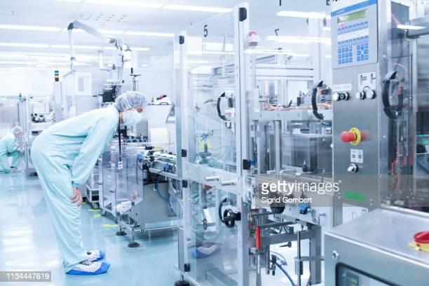 laboratory technician bending to take closer look at machine - sigrid gombert stock-fotos und bilder