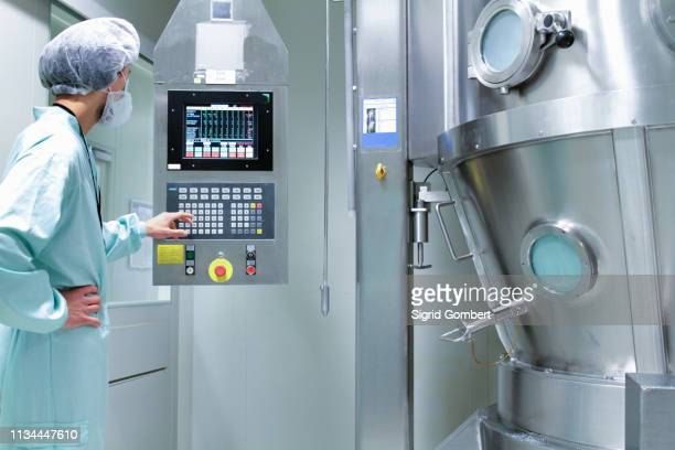 laboratory technician checking and adjusting equipment reading - sigrid gombert stock pictures, royalty-free photos & images