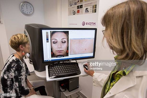 A laboratory technician right uses a desktop computer as antiaging facial skincare testing is carried out on a VISIACR Facial Imaging Booth...