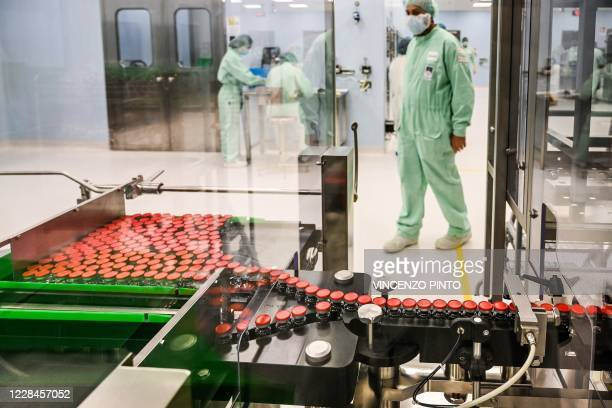 Laboratory technician supervises capped vials during filling and packaging tests for the large-scale production and supply of the University of...