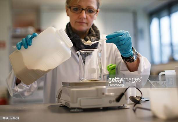 A laboratory technician weighs yeast extract powder in a glass beaker before application tests at the Royal DSM NV laboratory in Delft Netherlands on...