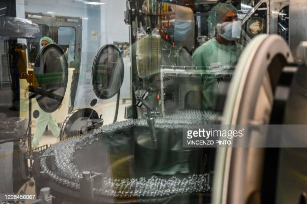 Laboratory technician, whose reflection can be seen supervises filling and packaging tests for the large-scale production and supply of the...