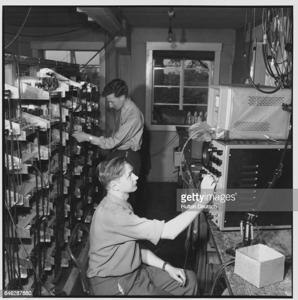 Laboratory workers check a transmitter rack and a waveform on a cathode ray oscillograph in the moon echo laboratory at Jodrell Bank Experimental...