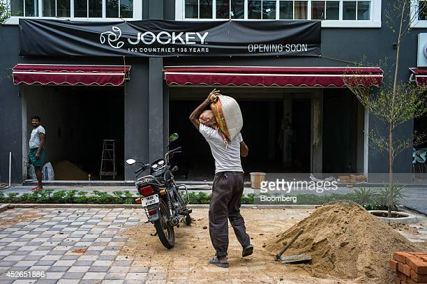 A laborer carries a bag of sand toward a Jockey store under renovation on Khader Nawaz Khan Road in Chennai Tamil Nadu India on Monday July 21 2014...