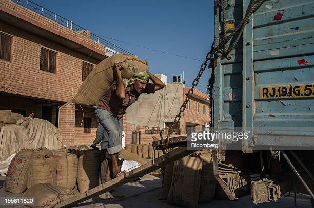 A laborer carries a sack of guar onto a truck at a grain market in Jodhpur India on Monday Oct 29 2012 Guar gum is used to blend materials used in...