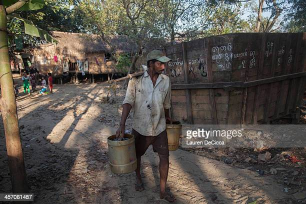 A laborer carries buckets of recycled oil to be placed into an oil drum on the banks of the Yangon River on December 16 2013 in Yangon Myanmar Large...