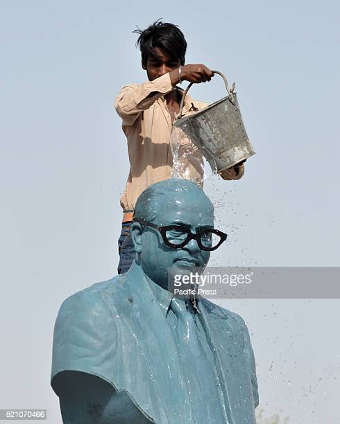A laborer cleaning the statue of Bhimrao Ambedkar on the eve of his birth anniversary in Bikaner