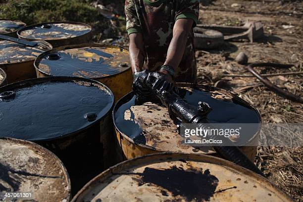 A laborer extracts oil from a cargo ship into 240kg drums for recycling on December 16 2013 in Yangon Myanmar Large cargo ships on the Irrawaddy...
