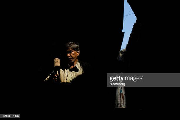 A laborer hammers metal at a workshop in the Dharavi slum area of Mumbai India on Friday Nov 9 2012 Indian industrial production unexpectedly fell in...