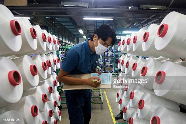 A laborer inspects polyester filament yarn on racks at the Indorama Polyester Industries Pcl Nakhon Pathom polyester facility operated by Ventures...