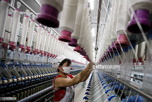 A laborer is seen working in a textile factory in Huaibei in north China's Anhui province on July 24 2013 China's manufacturing activity contracted...