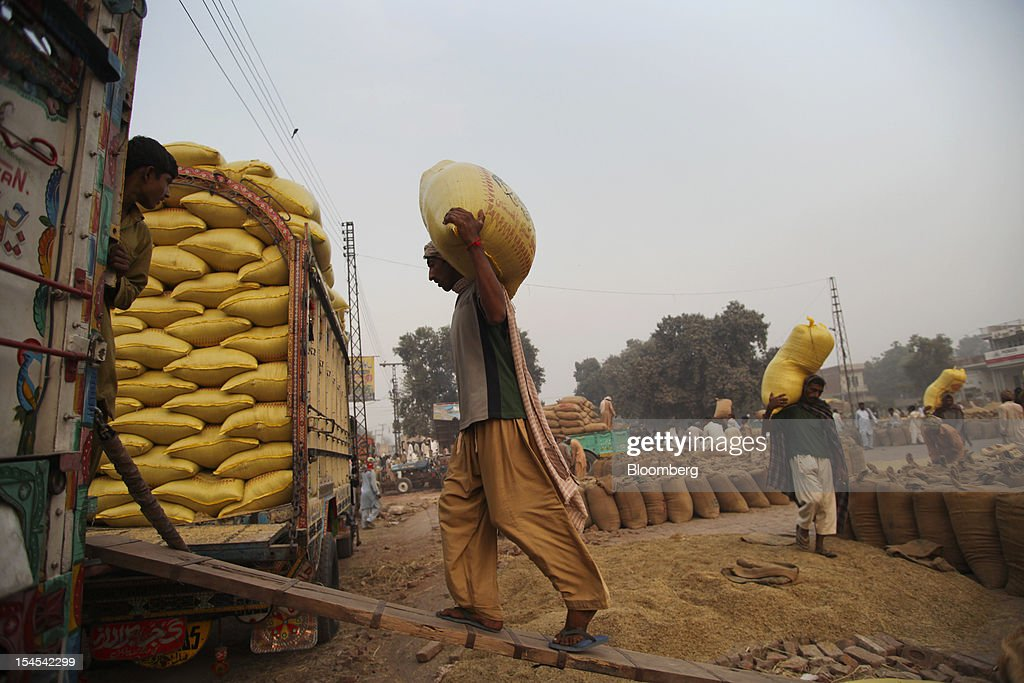 A laborer loads a bag of rice onto a truck at a rice market in the Chiniot district of Punjab province, Pakistan, on Saturday, Oct. 13, 2012. Rice exports from Pakistan, the fourth-largest shipper, are set to rebound from November with the new harvest after a rally in domestic prices and cheaper supplies from India cut shipments, a traders' group said. Photographer: Asad Zaidi/Bloomberg via Getty Images