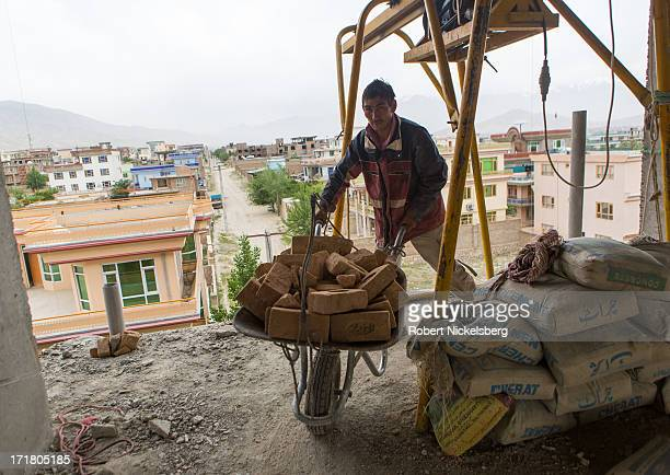 Laborer moves bricks inside a building under construction May 15, 2013 in the Omaid-e Sabz district of western Kabul, Afghanistan. Kabul's population...