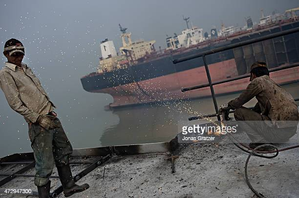 Laborer on top of a mega freighter that has been left on Chittagong beach is cutting through some railing to gather the scrap metal whilst...