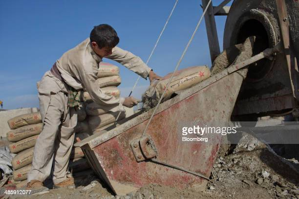 Laborer opens a bag of concrete as he works building concrete blast walls at a facility north of Kabul, Afghanistan, on Monday, April 14, 2014. The...