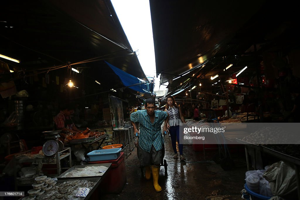 A laborer pulls a cart past seafood stalls at the Klong Thoei market in Bangkok, Thailand, on Sunday, Aug. 18, 2013. Thai economic growth slowed for a second quarter as exports cooled and local demand weakened, with rising household debt restricting the scope for monetary easing. Photographer: Dario Pignatelli/Bloomberg via Getty Images