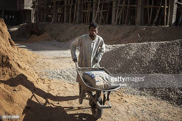 A laborer pushes bags of cement in a wheelbarrow on the construction site of a Saima Group residential housing project in Karachi Pakistan on Tuesday...