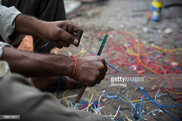 A laborer recovers copper from wiring in the Dharavi slum area of Mumbai India on Friday Nov 9 2012 Indian industrial production unexpectedly fell in...