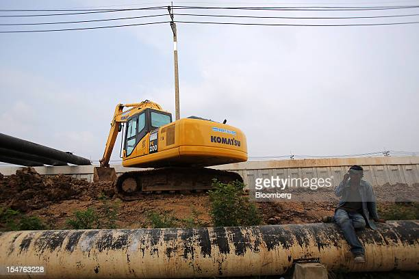 A laborer rests in front of a Komatsu Ltd excavator on the construction site of a floodprevention wall at Rojana Industrial Estate in Kanharm...