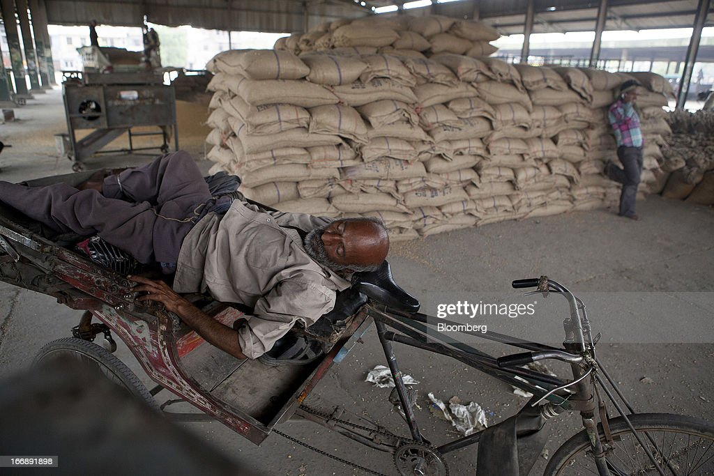A laborer rests on a rickshaw next to sacks of wheat at a grain market in the district of Jalandhar in Punjab, India, on Tuesday, April 16, 2013. Wheat harvest in India, the second-biggest grower, may reach a record for a sixth straight year after farmers increased use of high-yielding seeds and winter rains boosted crop prospects, a state-run researcher said. Photographer: Prashanth Vishwanathan/Bloomberg via Getty Images