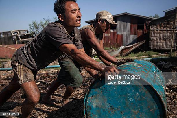 Laborer roll drums of recycled oil weighing 240kg on the banks of the Irrawaddy River in the Dala township of Yangon on December 16 2013 in Yangon...