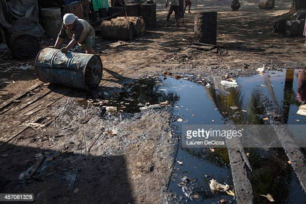 A laborer rolls recycled oil drums weighing 240kg on the banks of the Irrawaddy River in the Dala township of Yangon on December 16 2013 in Yangon...