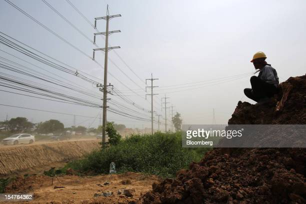 A laborer sits on the construction site of a new dike at HiTech Industrial Estate in Bang PaIn Ayutthaya province Thailand on Wednesday Oct 17 2012...