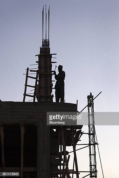 A laborer stands silhouetted while working on the construction site of a Saima Group residential housing project at dusk in Karachi Pakistan on...