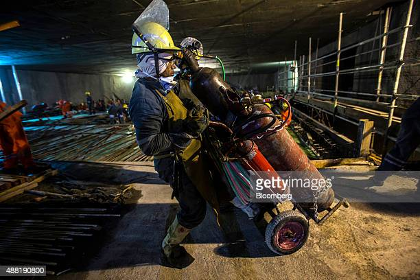 A laborer uses a hand truck to haul some materials during the construction of the Nossa Senhora da Paz metro station on the 4 Line of the subway...