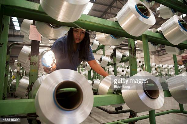 A laborer uses a light to inspect polyester filament yarn on racks at the Indorama Polyester Industries Pcl Nakhon Pathom polyester facility operated...