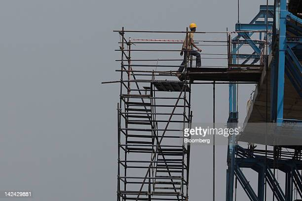 A laborer walks on a bridge construction over the Brahmaputra river in Guwahati India on Friday March 30 2012 Prime Minister Manmohan Singh's...
