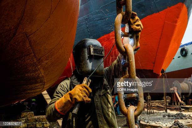 Laborer working at a shipyard near the Buriganga River. The shipbuilding industry in Bangladesh is spreading rapidly where workers from all ages work...
