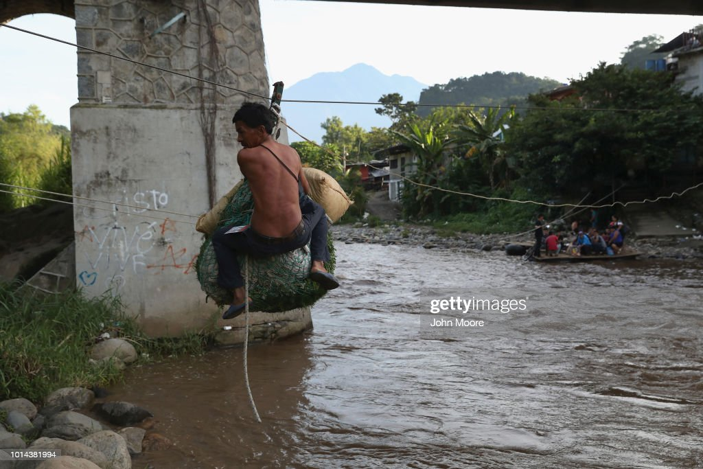 A laborer ziplines across the Suchiate River from Guatemala into Mexico on August 9, 2018 in Talisman, Mexico. The illegal crossing point is located just under the international bridge connecting the two countries, circumventing immigration and customs checkpoints.