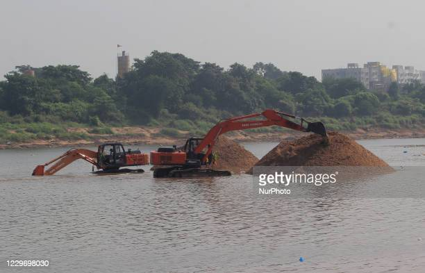 Laborers and other machines are seen inside the Kuakhai river as all are busy in the sand digging works to transport sands to the construction sites...