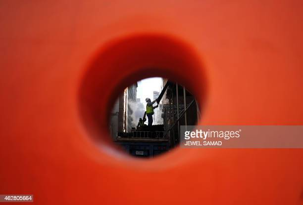 Laborers are seen through a hole of a safety barrier as they work at a building site in New York's Manhattan on February 5 2015 US privatesector...
