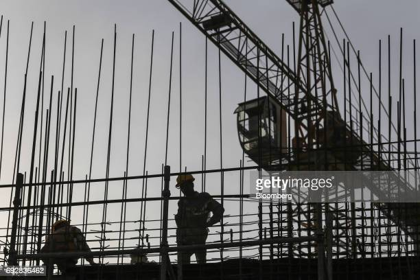 Laborers are silhouetted as they work at a construction site in Palava City on the outskirts of Mumbai India on Thursday May 25 2017 Lodha Group best...