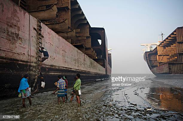 Laborers are walking on the muddy beach of Chittagong where mega freighters have been left for disassembling by poor workers. Where do the mega...