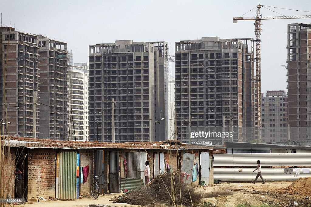 A laborers' camp stands in front of buildings under construction in Gurgaon, India, on Wednesday, March 26, 2014. Indian stocks rose, sending the benchmark index to a record, after the rupee rose to an eight-month high and sovereign bonds gained on speculation the worlds largest democracy will elect a government capable of reviving economic growth. Photographer: Kuni Takahashi/Bloomberg via Getty Images