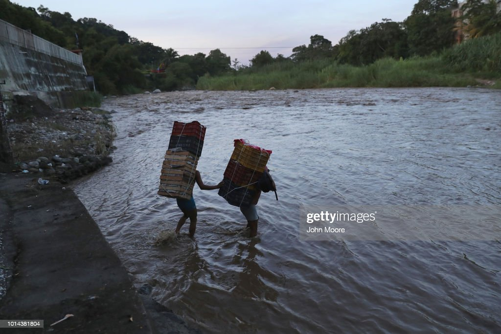Laborers carry goods across the Suchiate River from Guatemala into Mexico on August 9, 2018 in Carmen, Guatemala. The illegal crossing point is located just near the international bridge connecting the two countries, circumventing immigration and customs checkpoints.