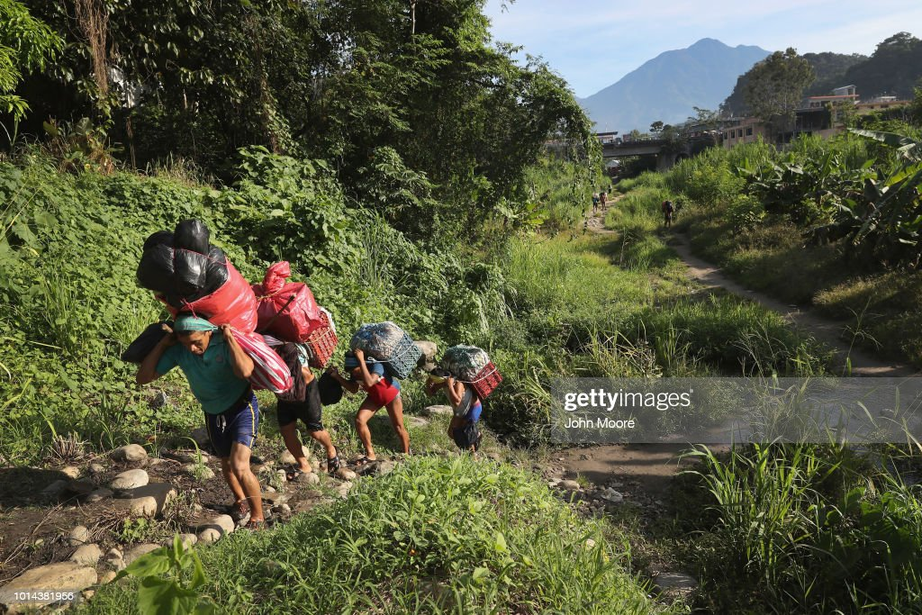 Laborers carry goods into Mexico after crossing the Suchiate River from Guatemala into Mexico on August 9, 2018 in Talisman, Mexico. The illegal crossing point is located just under the international bridge connecting the two countries, circumventing immigration and customs checkpoints.