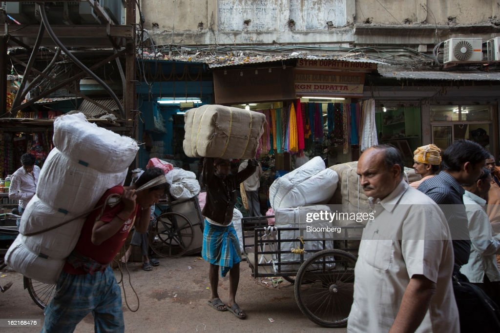 Laborers carry goods through the Burrabazar area of Kolkata, India, on Tuesday, Feb. 19, 2013. India's slowest economic expansion in a decade is limiting profit growth at the biggest companies even as foreigners remain net buyers of the nation's stocks, according to Kotak Institutional Equities. Photographer: Brent Lewin/Bloomberg via Getty Images