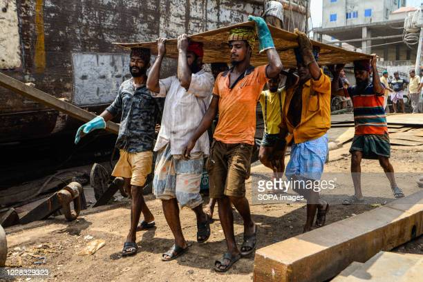 Laborers carrying a heavy equipment at a shipyard near the Buriganga River. The shipbuilding industry in Bangladesh is spreading rapidly where...