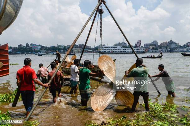 Laborers carrying a ship equipment at a shipyard near the Buriganga River. The shipbuilding industry in Bangladesh is spreading rapidly where workers...