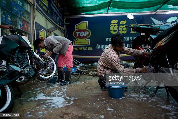 Laborers clean motorbikes at a car and motorcycle wash in Phnom Penh Cambodia on Friday Sept 25 2015 Moody's expects Cambodia's gross domestic...
