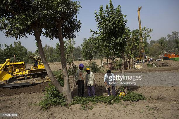 Laborers cut trees near a newly dug roadway April 22 2009 where agricultural areas members of twelve families have been farming for four generations...