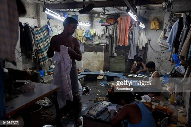 Laborers make leather wallets in a workshop in the Dharavi slums of Mumbai India on Saturday July 2009 Of the 19 million people who reside in Mumbai...
