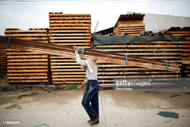 Laborers move bundles of wooden beams at a lumber trading yard in Anqing Anhui Province China on Tuesday July 12 2011 Log shipments from New Zealand...